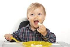 Kleiner kaukasischer Junge essen am Schätzchentisch Stockfotografie