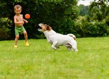 Kleiner Kinderjunge, der mit Hundewurf, Fang und Reichweitespiel spielt Lizenzfreies Stockbild