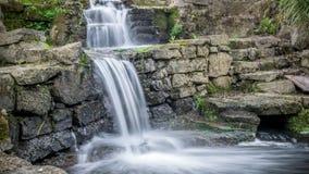 Kleiner kleiner Wasserfall in einem Steinpark in China Stockbilder