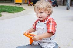 Kleiner Kleinkindjunge auf Auto auf Spielplatz Stockfotografie