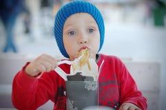 Kleiner Kleinkindjunge, der asiatisches Lebensmittel für das Mittagessen isst lizenzfreies stockbild