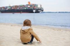 Kleiner Kleinkindjunge, der auf Sandstrand sitzt und auf containe schaut Lizenzfreie Stockbilder