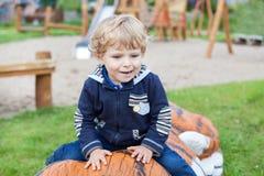 Kleiner Kleinkindjunge, der auf Spielplatz sitzt Stockbild