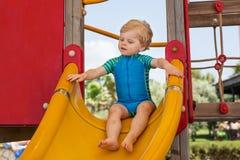 Kleiner Kleinkindjunge, der auf Spielplatz sitzt Lizenzfreie Stockfotos
