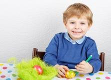 Kleiner Kleinkindjunge, der bunte Eier für Ostern-Jagd malt Lizenzfreie Stockfotos