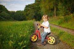 Kleiner Kleinkindjunge, der lernt, auf sein erstes Fahrrad zu fahren Stockfotos