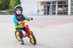 Kleiner Kleinkindjunge, der lernt, auf sein erstes Fahrrad zu fahren Stockbild