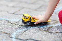 Kleiner Kleinkindjunge, der mit Autospielzeug spielt Lizenzfreie Stockbilder