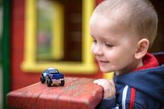 Kleiner Kleinkindjunge, der mit Autospielzeug spielt Selektiver Fokus an von Lächeln und Spaß habend Leasure-Abendspiel-Kinderkon Lizenzfreies Stockbild
