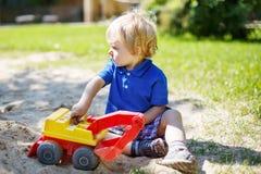 Kleiner Kleinkindjunge, der mit Sand und Spielzeug auf Spielplatz spielt Stockbild