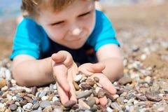 Kleiner Kleinkindjunge, der mit Sand und Steinen auf dem Strand spielt Lizenzfreie Stockbilder