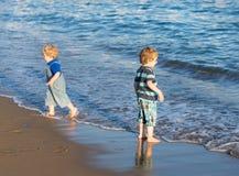 Kleiner Kleinkindjunge, der mit Sand und Steinen auf dem Strand spielt Stockfotos
