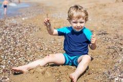 Kleiner Kleinkindjunge, der mit Sand und Steinen auf dem Strand spielt Lizenzfreies Stockbild