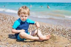 Kleiner Kleinkindjunge, der mit Sand und Steinen auf dem Strand spielt Lizenzfreies Stockfoto