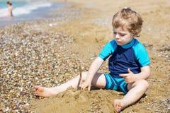 Kleiner Kleinkindjunge, der mit Sand und Steinen auf dem Strand spielt Stockfotografie