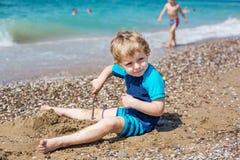 Kleiner Kleinkindjunge, der mit Sand und Steinen auf dem Strand spielt Lizenzfreie Stockfotos