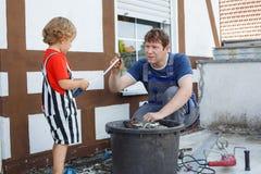 Kleiner Kleinkindjunge, der seinem Vater mit Erneuerung des Hauses hilft Stockbild