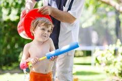 Kleiner Kleinkindjunge, der Spaß mit Spritzwasser im Sommerkaimanfisch hat Lizenzfreie Stockfotos