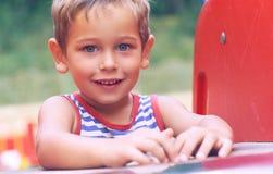 Kleiner Kleinkindjunge im gestreiften T-Shirt, das Spaß auf Spielplatz am Sommertag hat lizenzfreies stockbild
