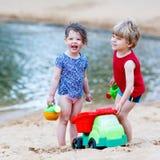 Kleiner Kleinkindjunge und -mädchen, die zusammen mit Sand spielt, spielt Lizenzfreie Stockfotos