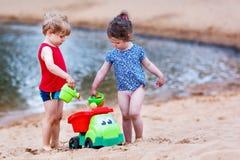 Kleiner Kleinkindjunge und -mädchen, die zusammen mit Sand spielt, spielt nahe Lizenzfreies Stockfoto