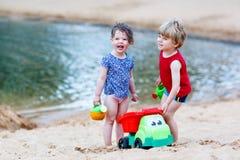 Kleiner Kleinkindjunge und -mädchen, die zusammen mit Sand spielt, spielt nahe Lizenzfreie Stockfotos