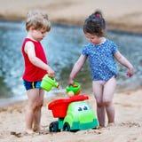 Kleiner Kleinkindjunge und -mädchen, die zusammen mit Sand spielt, spielt nahe Lizenzfreies Stockbild