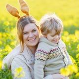 Kleiner Kleinkindjunge und seine Mutter in den Osterhasenohren, die Spaß haben Stockbilder