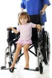 Kleiner Krankenhauspatient in einem Entlassungs-Rollstuhl Lizenzfreie Stockfotos
