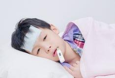 Kleiner kranker Junge, der auf Bett liegt Stockbild