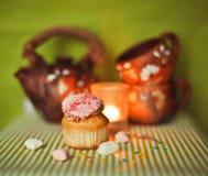 Kleiner Kuchen auf grünem Hintergrund mit Teepotentiometer und -cup Stockbilder