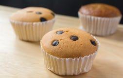 Kleiner Kuchen auf hölzernem und schwarzem Hintergrund Stockbild