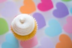 Kleiner Kuchen auf Herzhintergrund stockfotos