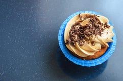 Kleiner Kuchen in den Kapseln der blauen Formen mit unterschiedlichem sahnt stockfoto