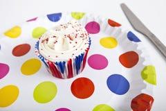Kleiner Kuchen in der mehrfarbigen Platte mit Tupfen gegen weißen Hintergrund lizenzfreie stockfotos
