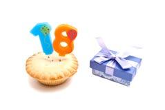 Kleiner Kuchen mit achtzehn Jahren Geburtstagskerze und -geschenk Stockfotografie