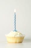 Kleiner Kuchen mit blauer Kerze Stockbild