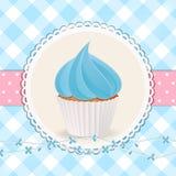 Kleiner Kuchen mit blauer Zuckerglasur auf blauem Ginghamhintergrund Stockfotos