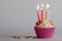 Kleiner Kuchen mit brennenden Kerzen Stockbilder