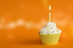 Kleiner Kuchen mit brennender Kerze Stockfotografie