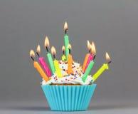 Kleiner Kuchen mit bunten Kerzen Lizenzfreies Stockfoto