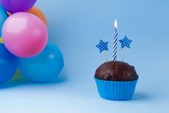 Kleiner Kuchen mit bunter Geburtstagskerze und -ballonen Lizenzfreie Stockbilder