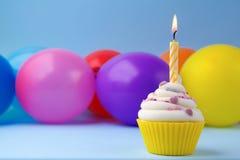 Kleiner Kuchen mit bunter Geburtstagskerze und -ballonen Lizenzfreies Stockfoto