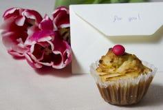 Kleiner Kuchen mit dem Buchstaben und ein Blumenstrauß auf einer Tabelle Stockbild
