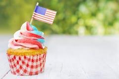 Kleiner Kuchen mit dem rot-weiß-und-blauen Bereifen und den amerikanischen Flaggen stockbild