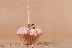 Kleiner Kuchen mit der brennenden festlichen Kerze Stockfotografie
