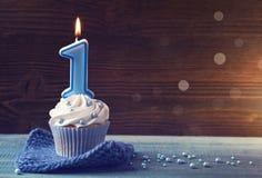Kleiner Kuchen mit einer blauen Kerze Stockbilder
