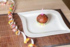 Kleiner Kuchen mit einer Geburtstagskerze auf Platte Lizenzfreie Stockbilder