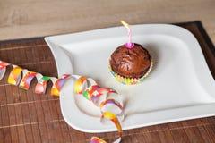 Kleiner Kuchen mit einer Geburtstagskerze auf Platte Lizenzfreie Stockfotos