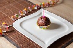 Kleiner Kuchen mit einer Geburtstagskerze auf Platte Stockfotografie